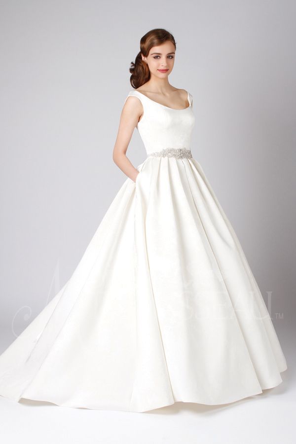 Satin ball gown wedding dress features a fully pleated skirt and off-the-shoulder bodice by Modern Trousseau. Made in the USA by Modern Trousseau.