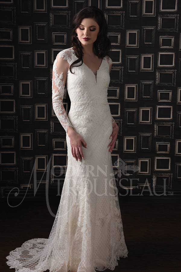 Fitted lace wedding dress features long sleeves with lace appliques and sweeping train by Modern Trousseau. Made in the USA by Modern Trousseau.