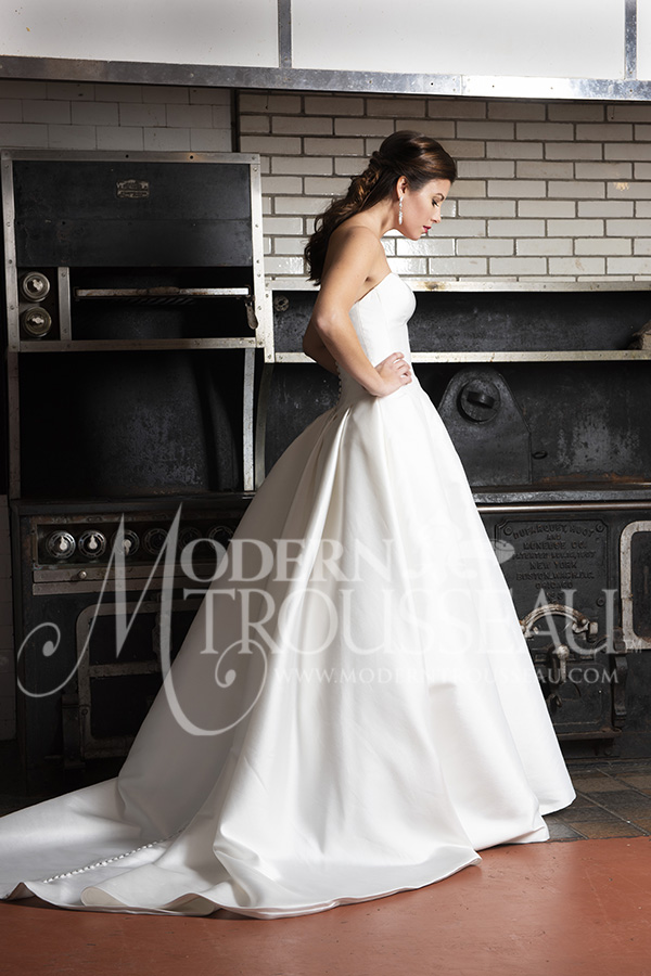 Strapless ballgown wedding dress features drop waist and buttons down the back by Modern Trousseau. Made in the USA by Modern Trousseau.