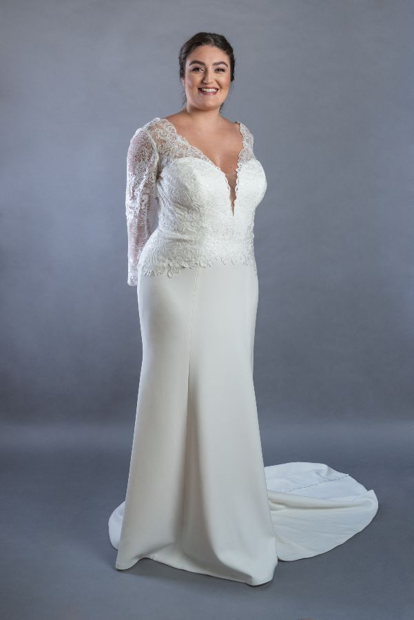 Bride wearing long sleeve wedding gown with crepe botton