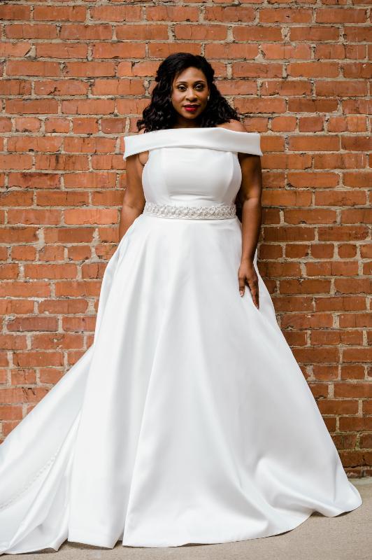 plus size bride against brick wearing ballgown wedding dress
