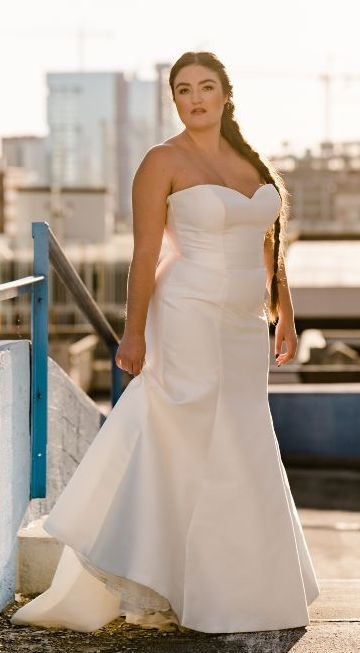 Strapless white fitted wedding gown, Bride has braided hair.